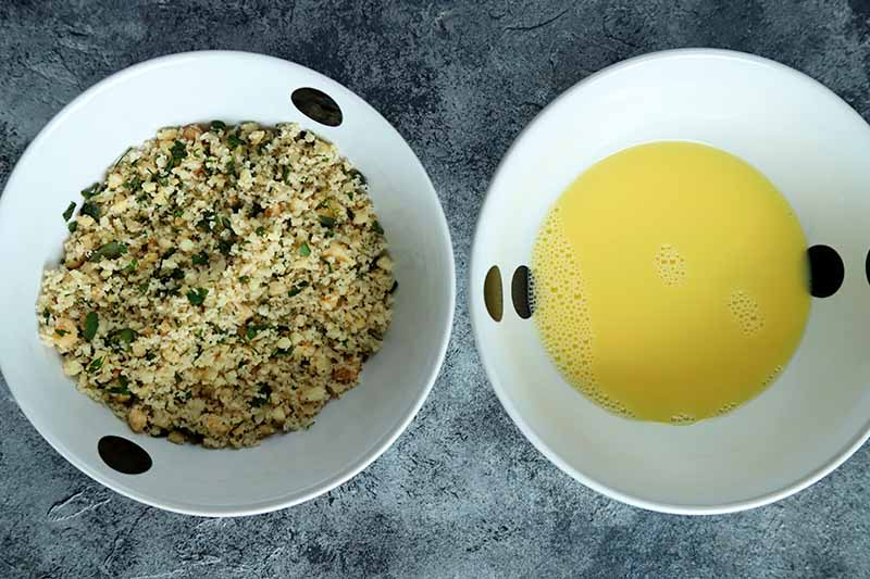 Overhead horizontal image of two shallow white bowls with a pattern of black spots, filled with an herb, breadcrumb, and nut mixture on the left, and pale yellow egg wash on the right, on a mottled dark gray and white surface.