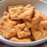 Horizontal image of square orange bite-sized crackers in a white bowl, on a surface topped with a red and white checkered cloth.