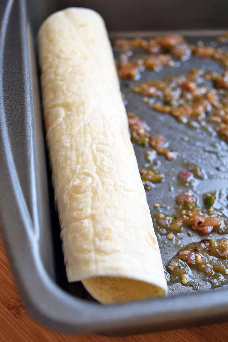 Horizontal image of a rolled flour tortilla positioned against the left wall of a metal baking pan with salsa spread in the bottom, on a brown surface.