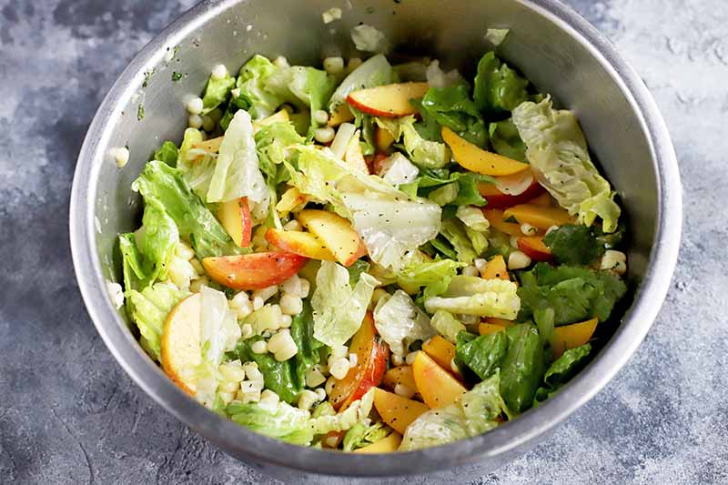 Horizontal image of mixed lettuce greens with sliced fresh stone fruit and corn.
