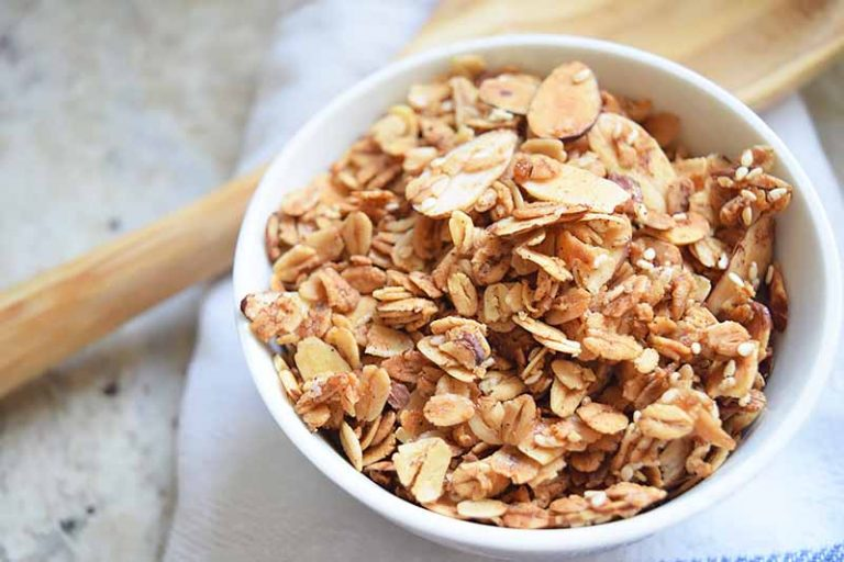 Horizontal image of a white bowl with an oat mixture on a white towel next to a wooden spoon.