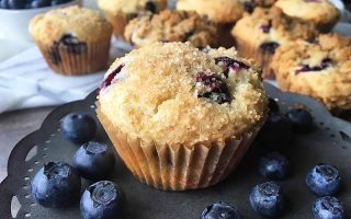 Horizontal image of blueberry muffins on a dark pan with fresh fruit surrounding them.