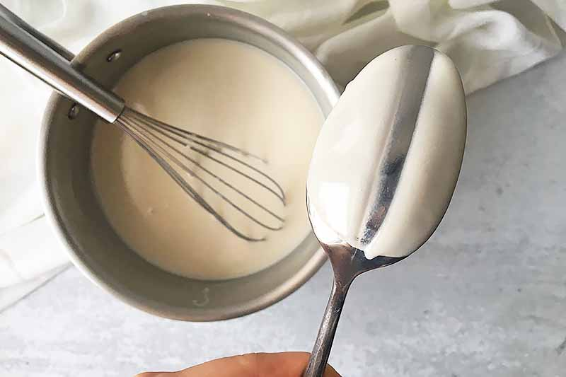 Horizontal image of a hand holding a metal spoon covered in a thick white liquid with a line drawn down it, over a pot of white liquid with a whisk in it.