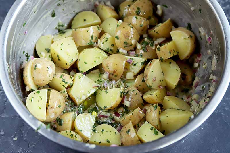 Horizontal image of a metal bowl with an herbed potato side dish.