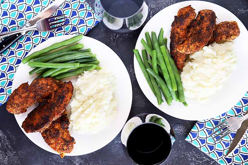 Horizontal image of two white plates with blackened tenders, green beans, mashed potatoes, napkins, and glasses of red wine.