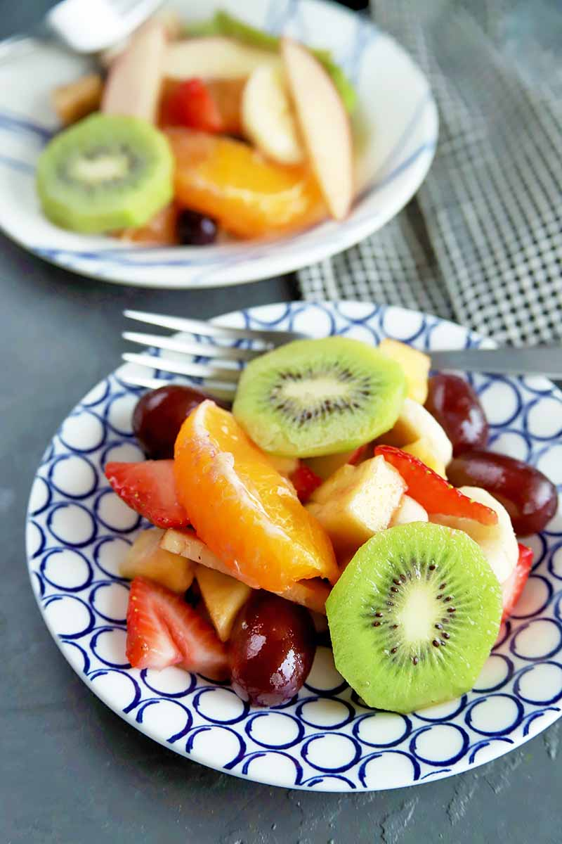 Vertical image of two plates with assorted cut kiwi, orange, grapes, and strawberries.