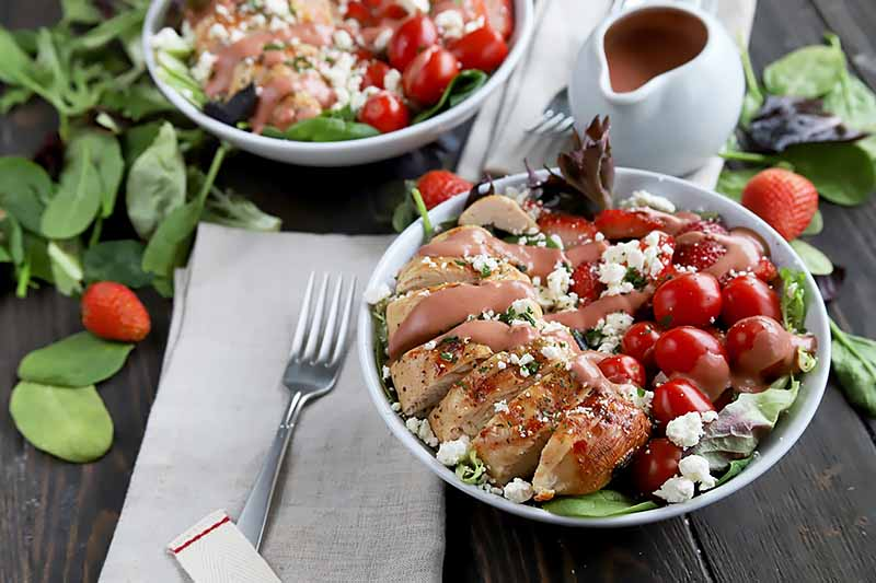 Horizontal image of two plates with sliced grilled chicken and tomatoes on a bed of lettuce, next to white napkins, metal forks, spinach leaves, and a white vessel of pink dressing.
