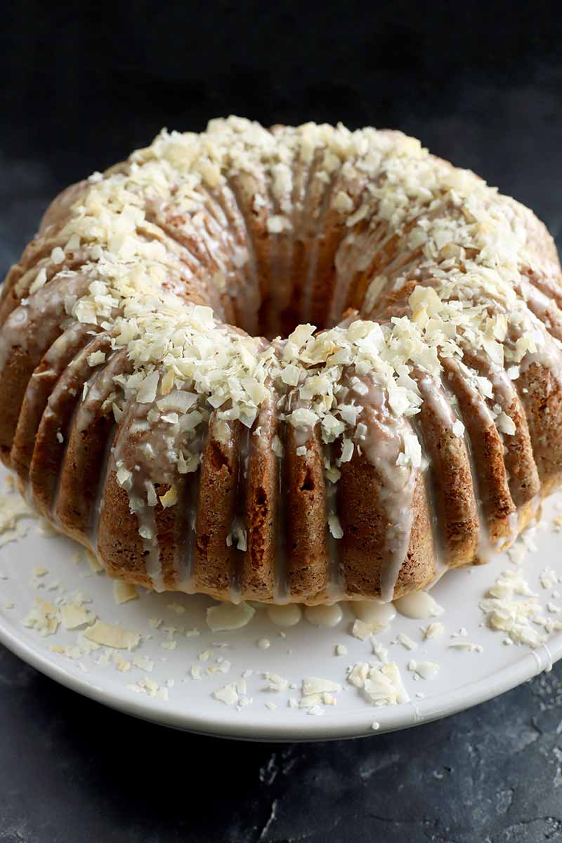 Vertical image of a whole bundt cake with glaze and garnishes.