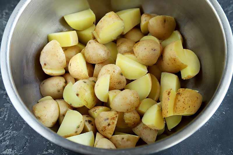 Horizontal image of steamed sliced potatoes in a metal bowl.