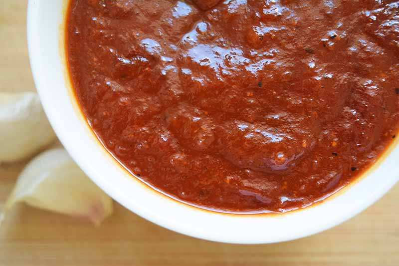Overhead closely cropped horizontal image of a white bowl filled with a red, homemade, tomato-based puree made with chipotles and onion, with two cloves of garlic on a beige wood surface.