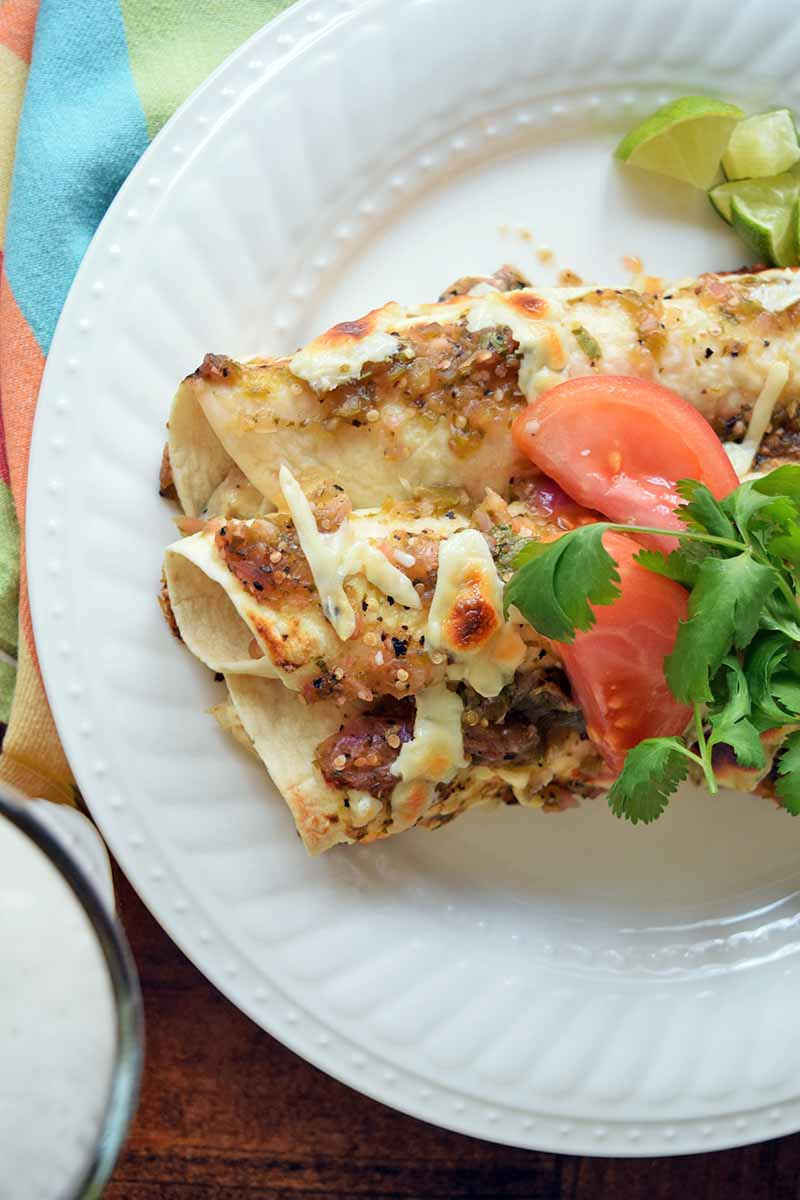 Vertical overhead image of a white ceramic plate of chicken enchiladas with tomato slices and fresh cilantro, on a wood table with a glass of beer and a colorful striped cloth.