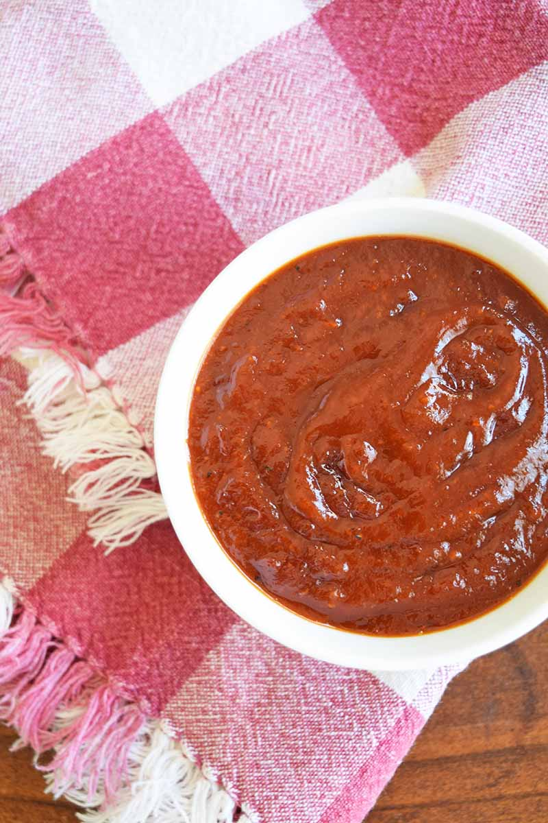 Overhead vertical image of a white bowl of red Texas-style barbecue sauce on a folded red and white cloth with fringe, on top of a brown wood surface.