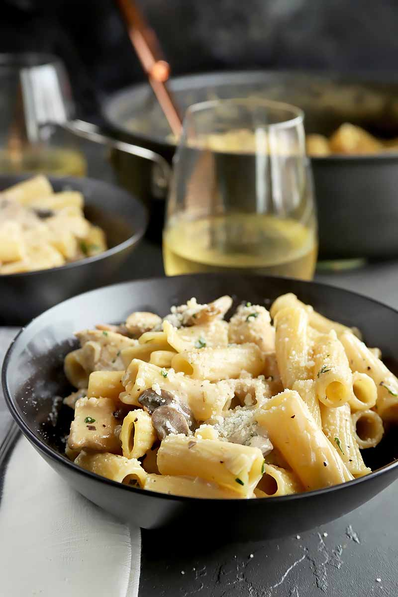 Vertical image of two bowls of Maggiano's Rigatoni Di Gregario, next to a large block skillet and a glass of white wine.