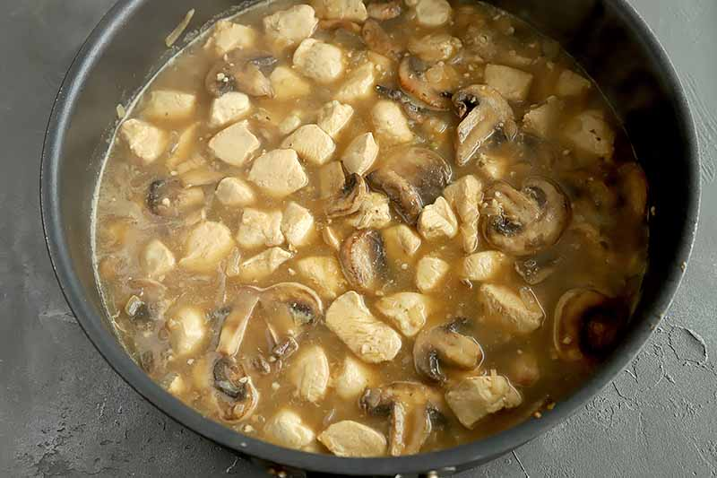 Horizontal image of a skillet with chicken and mushrooms cooking in a brown mixture.