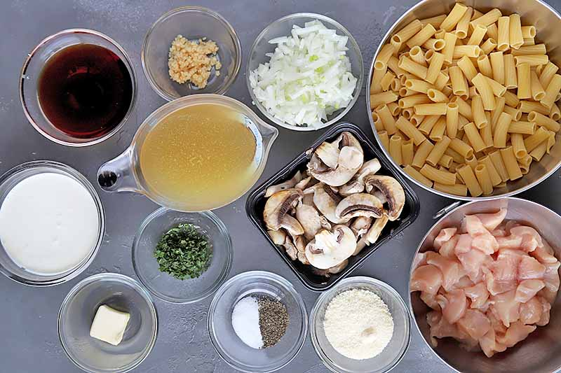 Horizontal image of assorted ingredients in bowls to make Rigatoni Di Gregario on a gray surface.