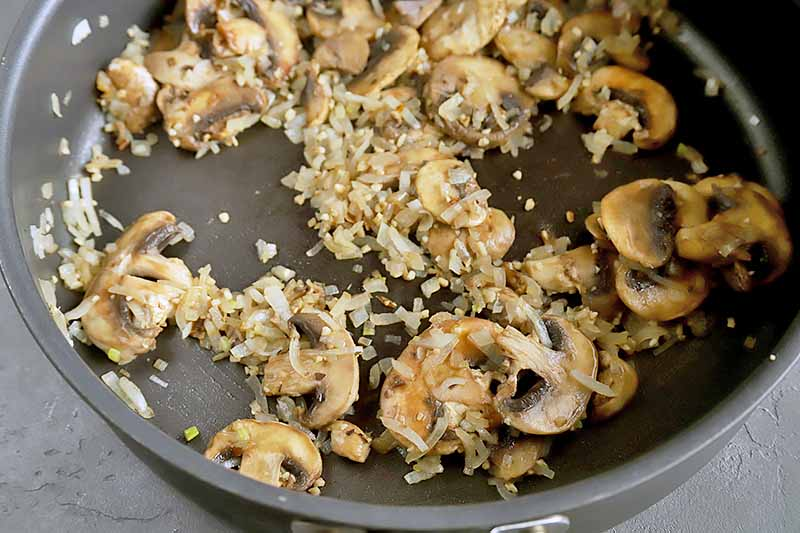 Horizontal image of a skillet with cooked garlic, onions, and sliced mushrooms.