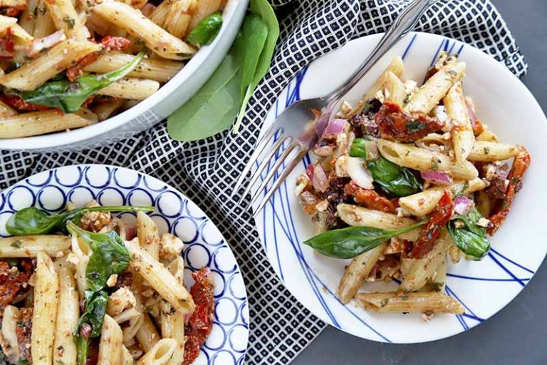 Overhead horizontal image of two blue and white plates and a white serving bowl of penne pasta salad with spinach and sun-dried tomatoes, on a gray surface partially covered with a black and white checkered cloth, with scattered leafy greens.