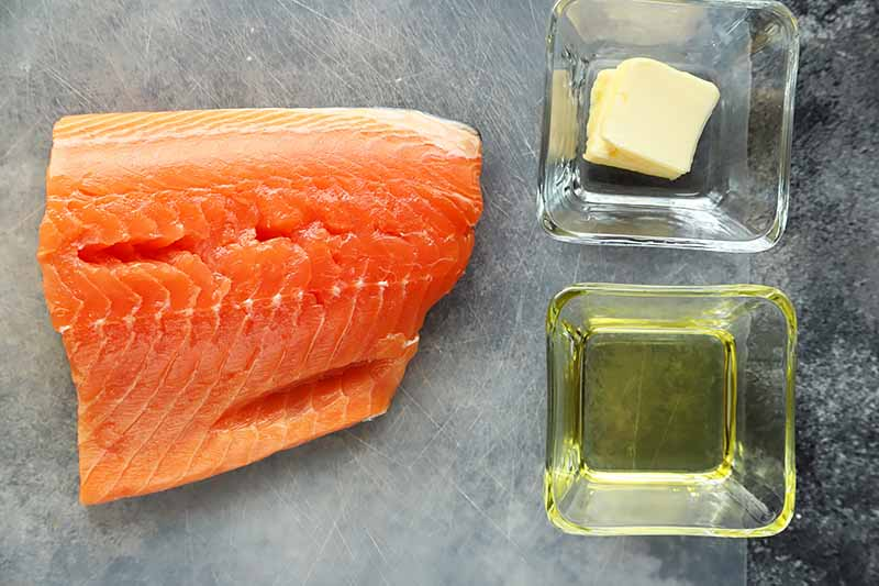 Horizontal image of a raw salmon fillet next to glasses of oil and butter.