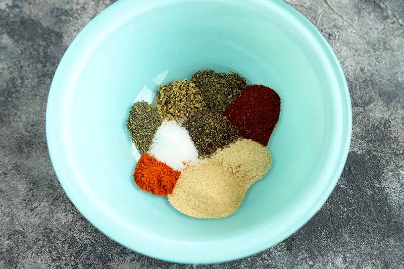 Horizontal image of a blue bowl with assorted spices.