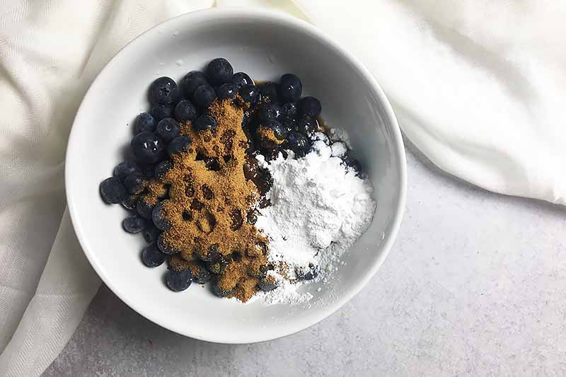 Horizontal image of dry ingredients on top of fresh blueberries in a white bowl.