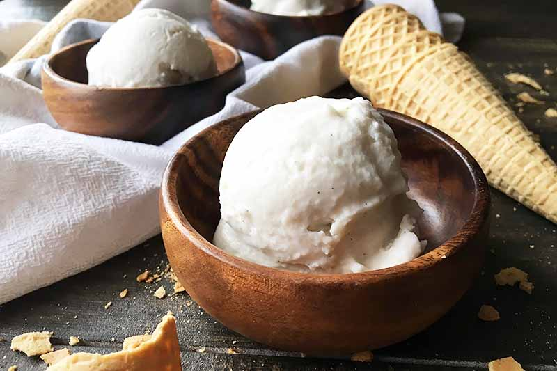 Horizontal image of three wooden bowls with scoops of white ice cream on a white towel next to cones.