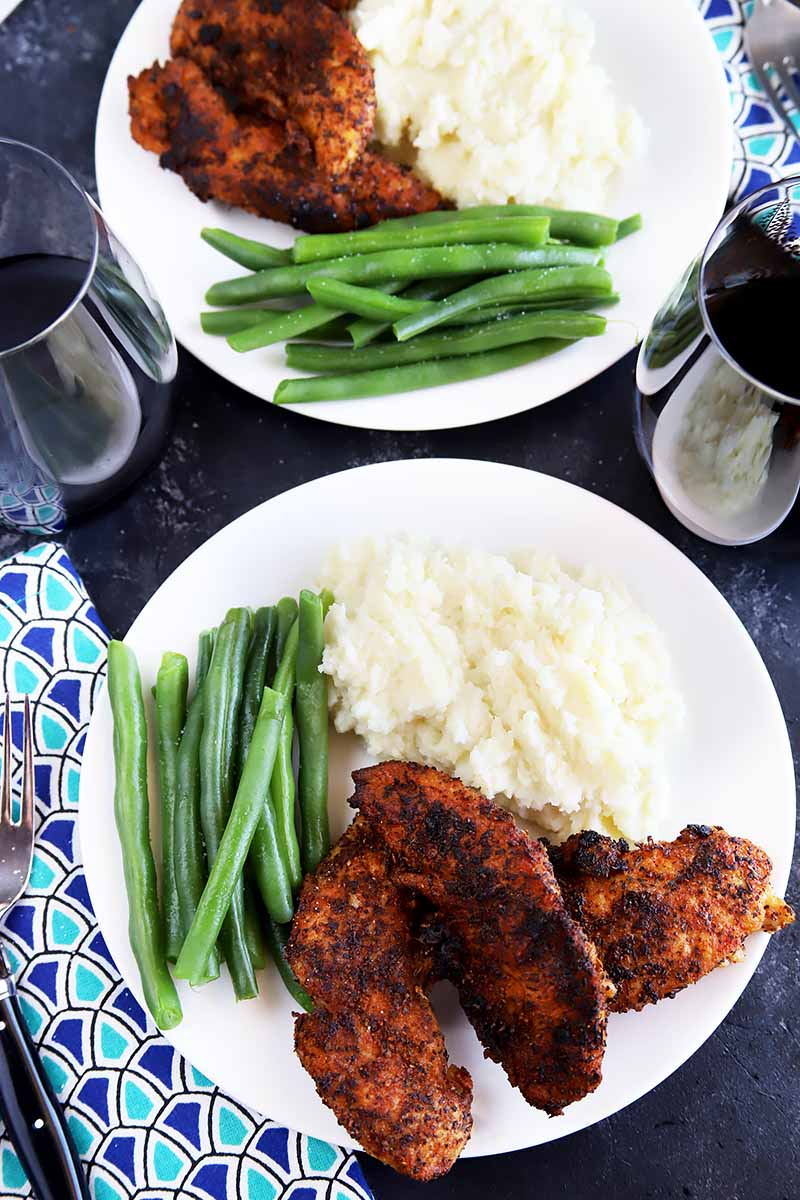 Vertical top-down image of two plates with green beans, mashed potatoes, and spiced tenders next to glasses of red wine.