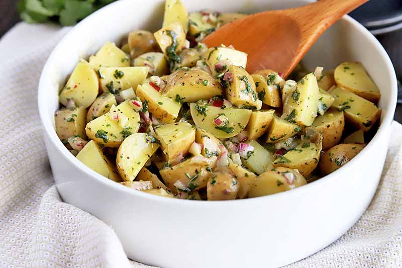 Horizontal image of a white bowl filled with herbed potato salad with a wooden spoon.