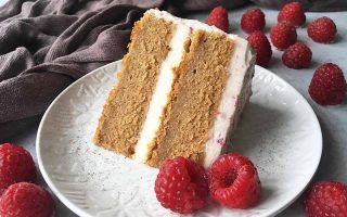 Horizontal image of a two-layer spelt cake with a white filling and light pink frosting on a white plate garnished with raspberries.
