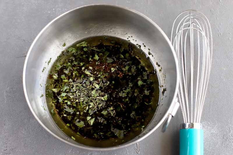 An oil, vinegar, and herb mixture in a stainless steel mixing bowl with a ring handle, with a blue-handled wire whisk to the right, on a gray surface.