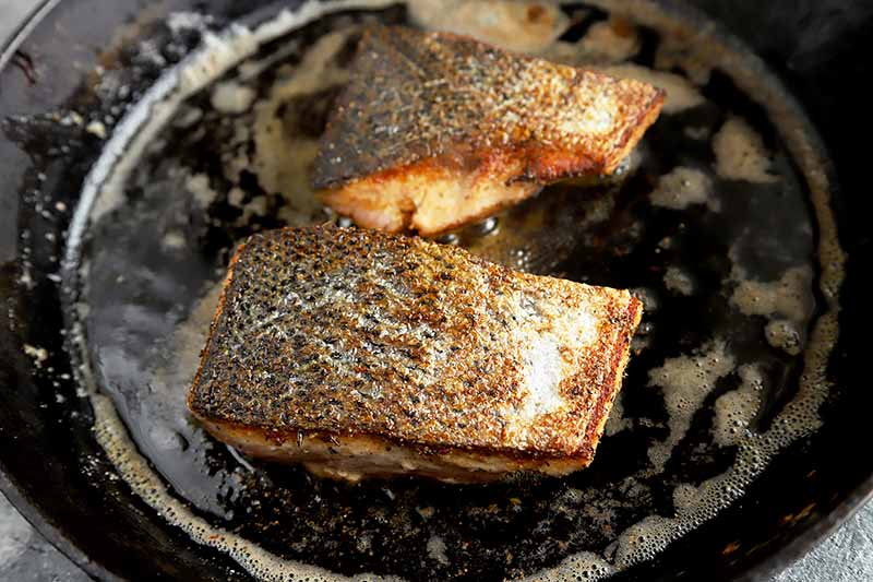 Horizontal image of two salmon fillets with crispy skins cooking in a skillet.