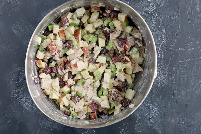 Overhead horizontal image of a slightly misshapen metal bowl filled with chicken salad, on a gray surface.