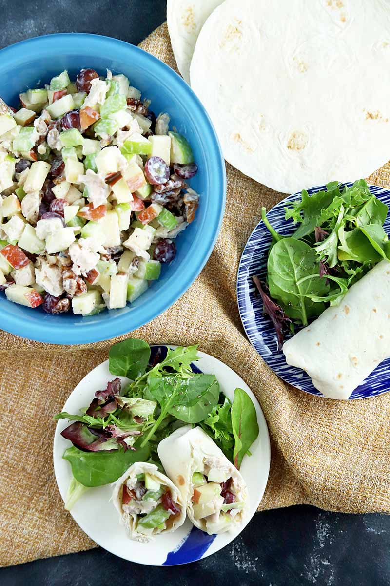 Overhead vertical image of a blue glass bowl of chicken salad with fruit and nuts, and two wraps on blue and white plates with green salads, and a stack of flour tortillas at the top left corner of the frame, on a folder piece of light brown burlap on top of a gray slate surface.
