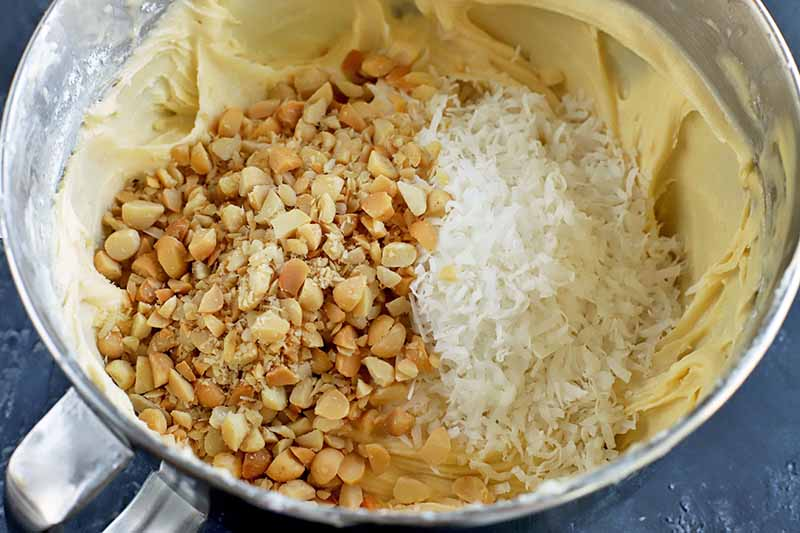 Horizontal image of a bowl with batter and topped with nuts and coconut.