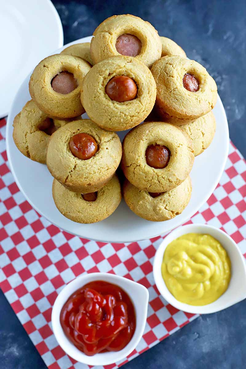 Vertical oblique overhead image of corn dog muffins arranged on a white creamic cake stand with two small white bowls of ketchup and mustard in the foreground on a red and white checkered paper liner, with a white plate at the top left of the frame, on a dark gray background.
