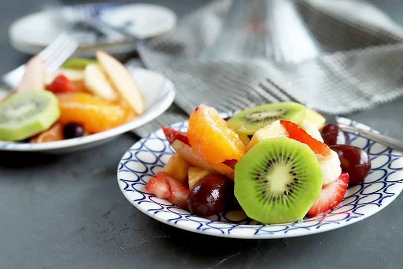 Horizontal image of two plates with assorted fresh cut summer produce next to metal forks.