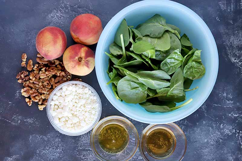 Overhead view of a light blue glass bowl of baby spinach with smaller glass bowls of honey, oil, and crumbled goat cheese to the left, a pile of chopped walnuts, and three fresh peaches, on a gray stone surface.