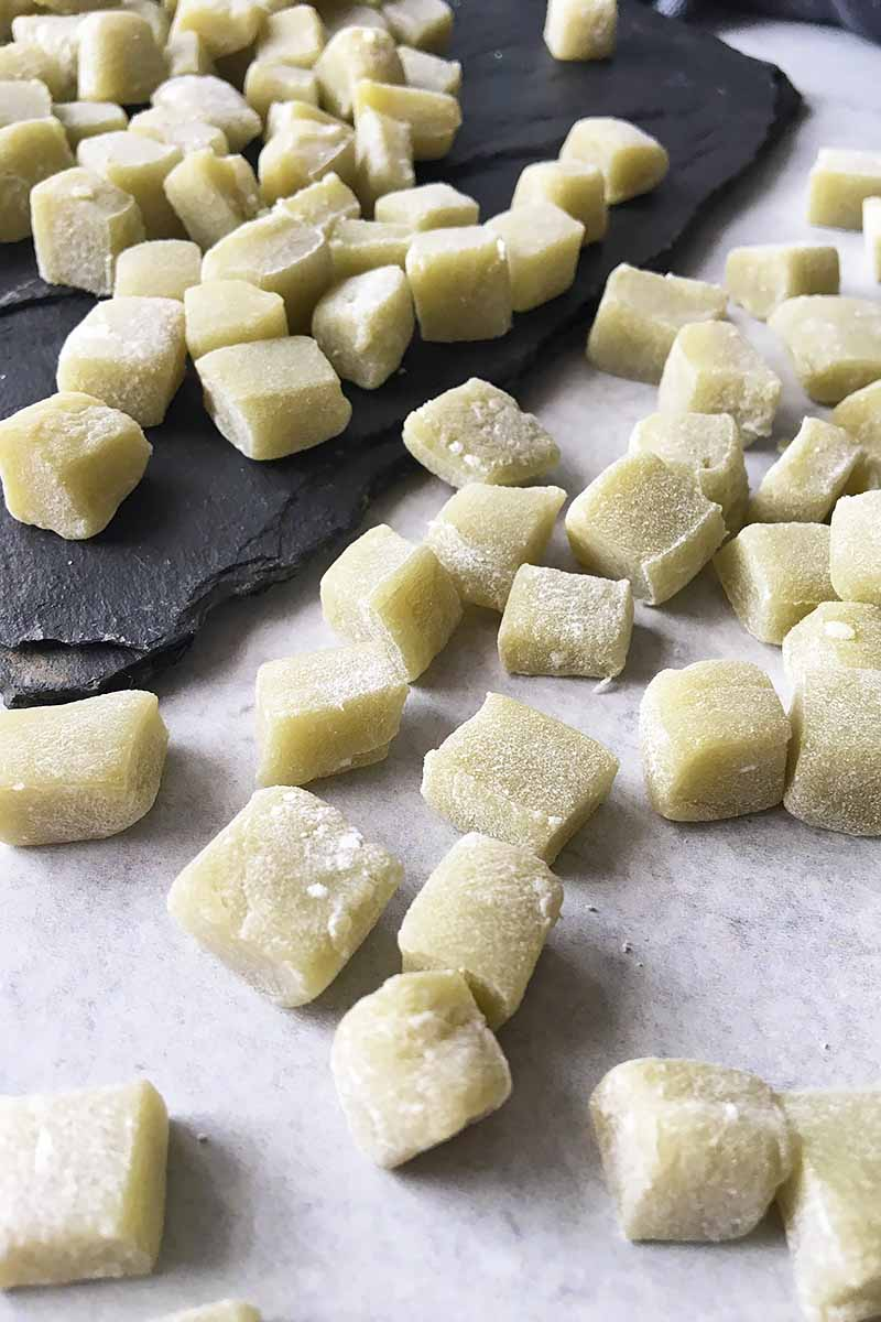 Vertical image of bites of mochi, some on a dark slate.