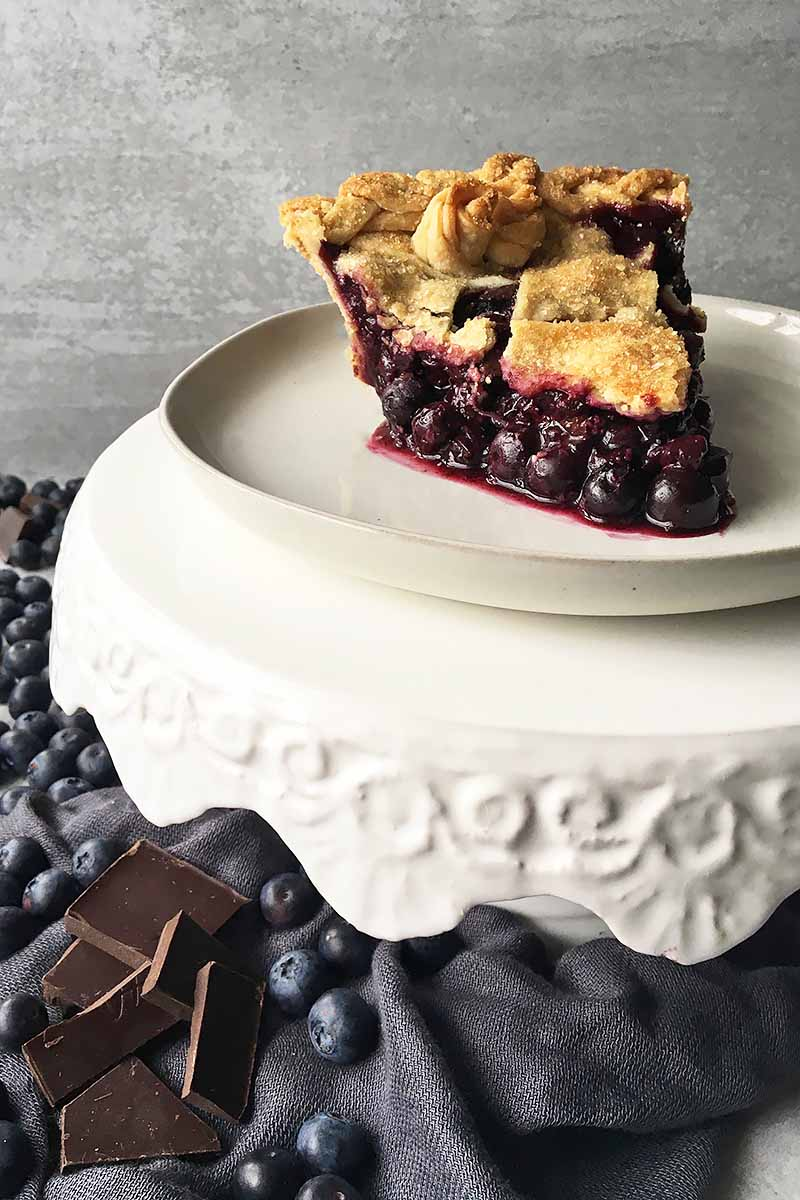 Vertical image of a plate on a stand with a slice of blueberry pie, next to fresh fruit and candy chunks.