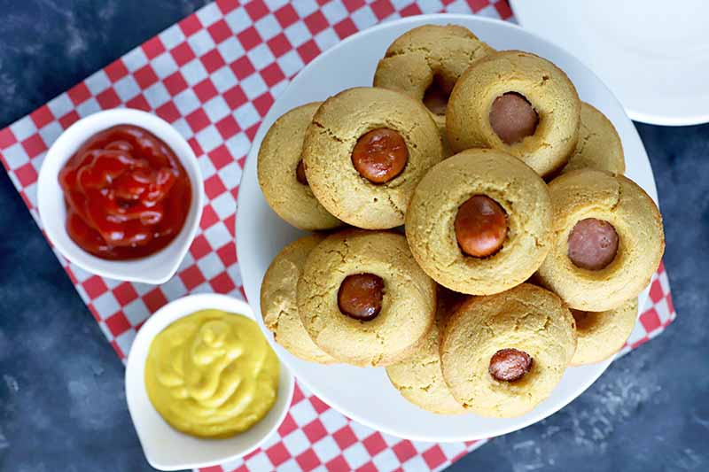 Overhead horizontal image of about a dozen corn dog muffins arranged on a white platter, with two small white bowls of ketchup and yellow mustard to the left on a red and white checkered paper liner, with a white plate at the top right corner of the frame, on a dark gray background with white marks.
