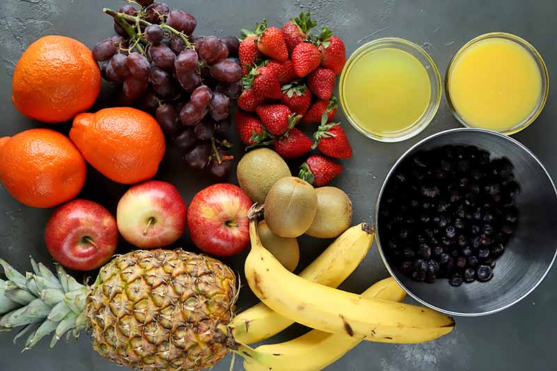 Horizontal image of assorted fresh fruits on a gray surface.