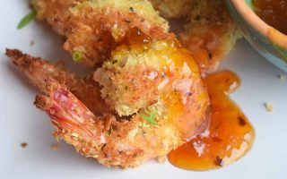 Horitonal closeup image of several baked coconut shrimp with sweet and sour sauce.