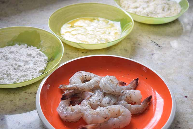 Horizontal image of three shallow green glass bowls of flour, beaten egg, and a mixture of coconut flakes and panko breadcrumbs arranged in a row in the background, with an orange plate of raw shrimp with the tails on in the foreground, on a speckled off-white countertop.