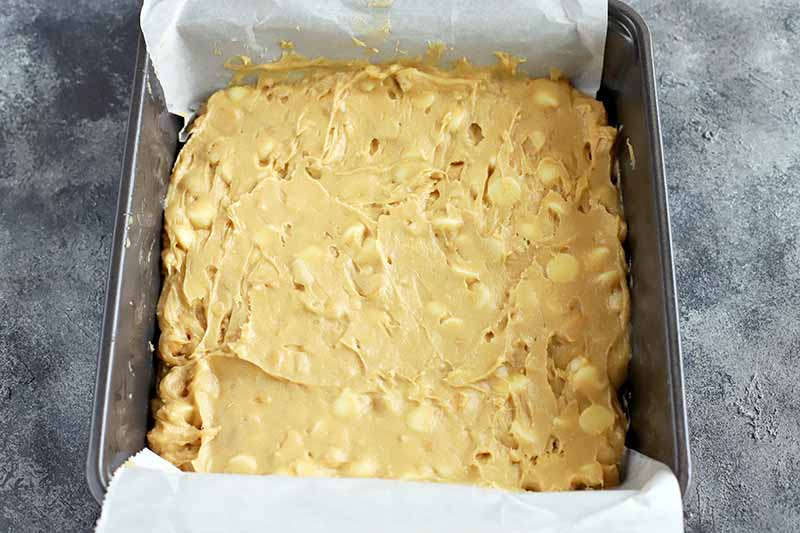 Horizontal image of a blondie batter in a pan with parchment paper.