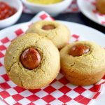 Horizontal closeup image of three corn dog muffins arranged on a white plate on top of a red and white paper liner, with another plate of the same and two small white dishes of ketchup and mustard in the background, on a dark gray stone surface.