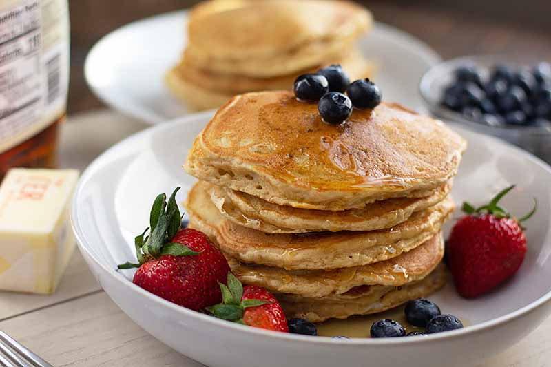 Horizontal image of a stack of flapjacks topped with syrup and blueberries.