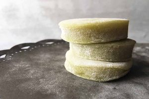 Horizontal image of a stack of three circular mochi desserts on a gray plate.