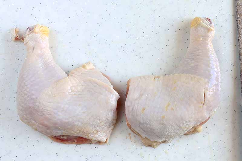Horizontal image of joined chicken thighs and drumsticks.
