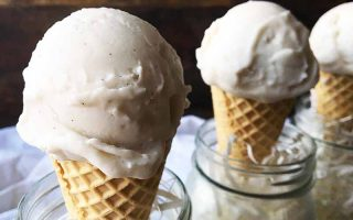 Horizontal image of three cones with scoops of white ice cream in glass mason jars.