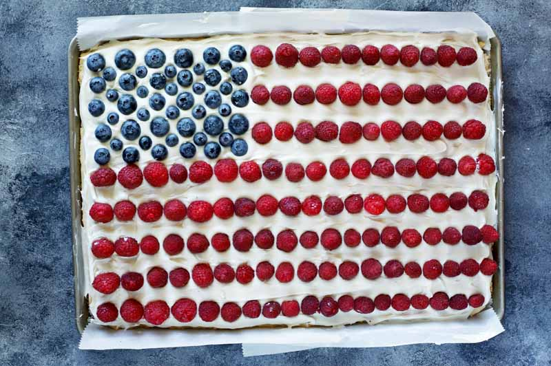 Top down view of a cookie cake shaped like an American flag with blueberries forming the blue field and cream frosting and strawberries forming the white and red stripes.