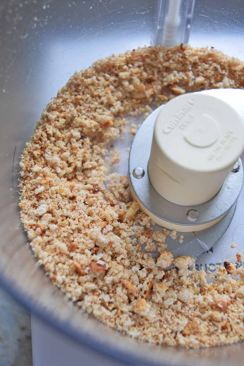 Vertical overhead closely cropped image of breadcrumbs in a food processor.
